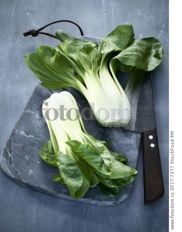 Bok choy on a grey marble board with a knife