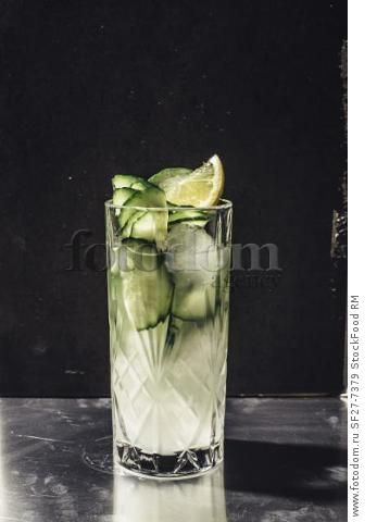 Cucumber gin with tonic in a kirstall glass against a dark background