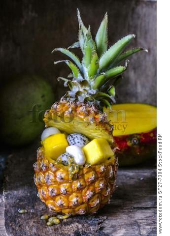 Fruit salad in pineapple on a wooden background