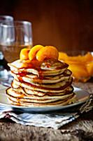 Stack of homemade pancakes with poached peaches
