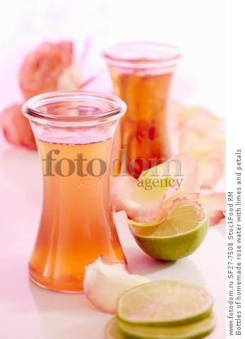 Bottles of homemade rose water with limes and petals