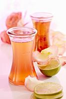Bottles of homemade rose water with limes and peta