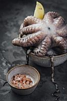 Fresh octopus in a bowl with lemon and pink salt