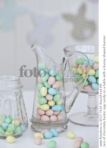 Jars of chocolate Easter egg candy on a table with a bunny shaped banner