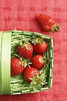 Fresh strawberries in a green plastic basket