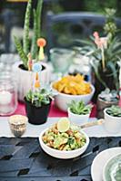 Guacamole and potted succulents on table set for M