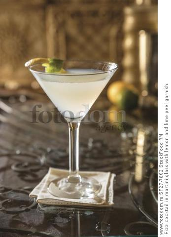 Fizz cocktail in martini glass with lemon and lime peel garnish