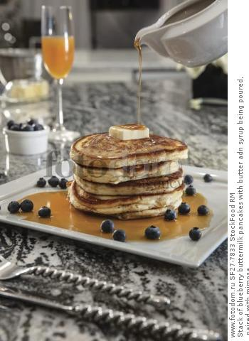Stack of blueberry buttermilk pancakes with butter adn syrup being poured, paired with mimosa