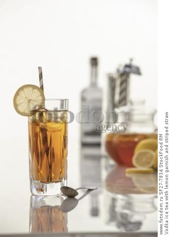Vodka ice tea with lemon garnish and striped straw