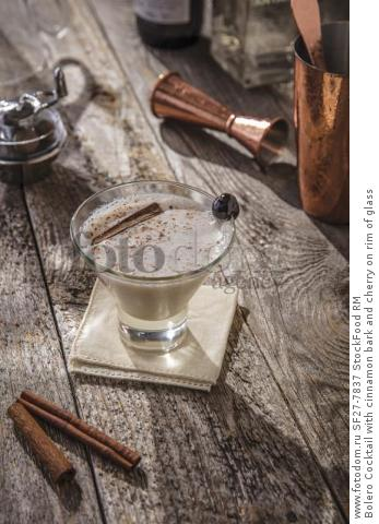 Bolero Cocktail with cinnamon bark and cherry on rim of glass