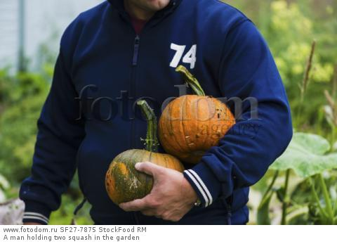 A man holding two squash in the garden
