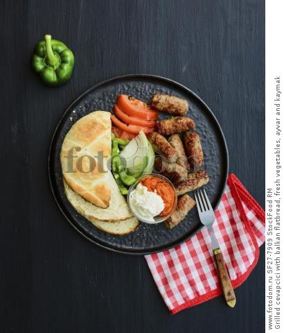 Grilled cevapcici with balkan flatbread, fresh vegetables, ayvar and kaymak