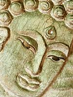 Buddha's face close up. Wooden relief.