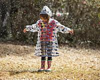 Little girl in raincoat and boots playing in the r