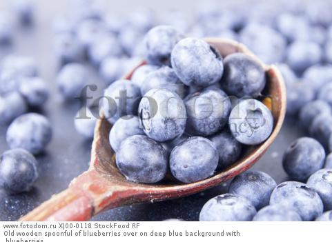 Old wooden spoonful of blueberries over on deep blue background with blueberries