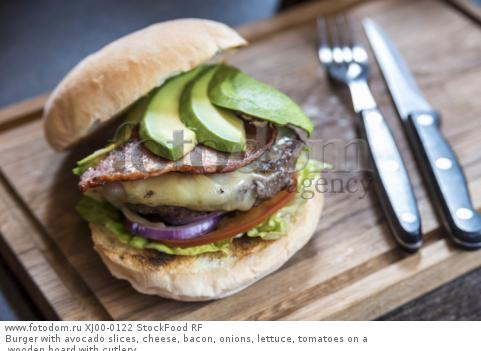Burger with avocado slices, cheese, bacon, onions, lettuce, tomatoes on a wooden board with cutlery