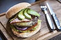 Burger with avocado slices, cheese, bacon, onions,