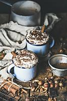 Hot chocolate in blue mugs with whipped cream and