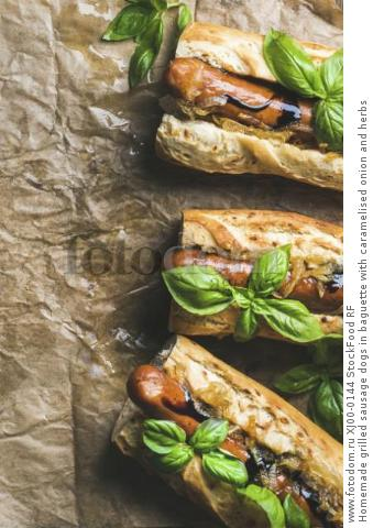 Homemade grilled sausage dogs in baguette with caramelised onion and herbs