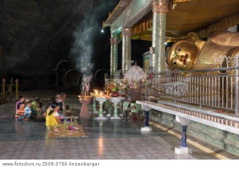 MYANMAR / Kayin State / Hpa-an / Burmese believers praying in front of a reclining Buddha image. Before they donated incense sticks, candles and flowers. Saddar Cave housed many Buddha statues, mural reliefs and pagodasВ© Mario Weigt / Anzenberger