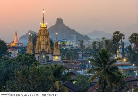 MYANMAR / Kayin State / Hpa-an / Evening mood in Hpa-an. Townscape with Ye Kyaung Monastery and Shwe Yin Myaw Pagoda. In the background is the Hpan Pu limestone mountain on the other side of the Thanlwin River