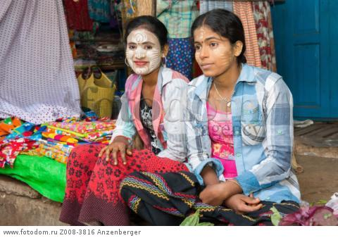 MYANMAR / Kayin State / Hpa-an / Market vendors with Thanaka on the face waiting for customers. The yellowish-white paste made from ground bark of the wood-apple tree (Limonia acidissma) and water is used as sun blocker and make-up. В© Mario Weigt / Anzenberger