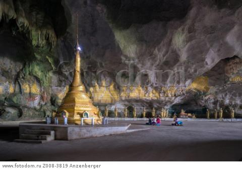 MYANMAR / Kayin State / Hpa-an / Buddhists praying in front of a golden stupa. Saddar Cave housed a lot of Buddha statues, mural reliefs and pagodasВ© Mario Weigt / Anzenberger