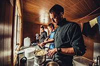 man cooking in a cabin, greenland, arctic.