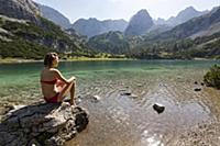 Girl in bikini sitting at Lake Seebensee with Drac