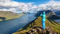 Young woman looks over the fjord landscape, the mo