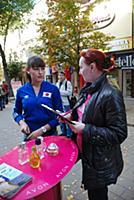 Женщина-промоутер предлагает парфюмерию на улице.