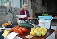 Пожилая женщина продает ягоды, овощи и фрукты свое