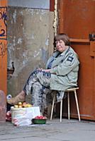 Женщина торгует яблоками и грушами, сидя на крыльц