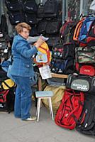 Женщина торгует сумками на улице.