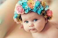 Улыбающийся ребенок с венком из роз