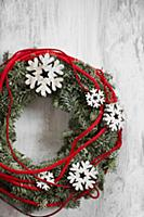 Wreath decorated with wooden snowflakes and red co
