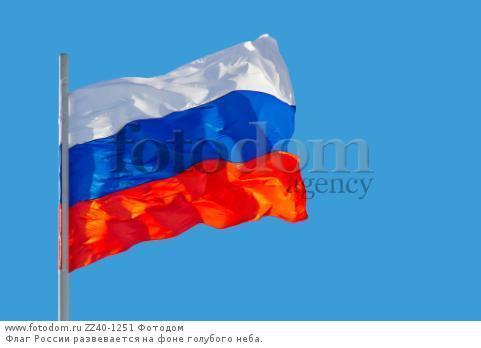 Флаг России развевается на фоне голубого неба.