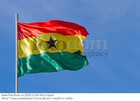 Флаг Ганы развевается на фоне голубого неба.