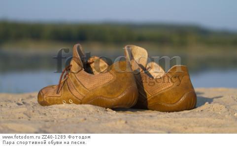 Пара спортивной обуви на песке.