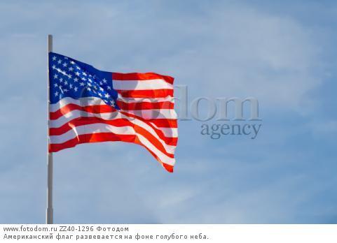 Американский флаг развевается на фоне голубого неба.
