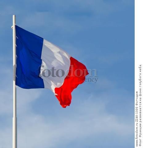 Флаг Франции развевается на фоне голубого неба.