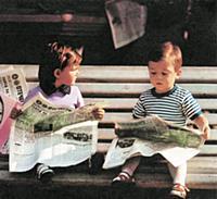 Дети читают свежие выпуски газет на скамейке в пар