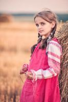 Девочка в русской народной одежде у стога сена