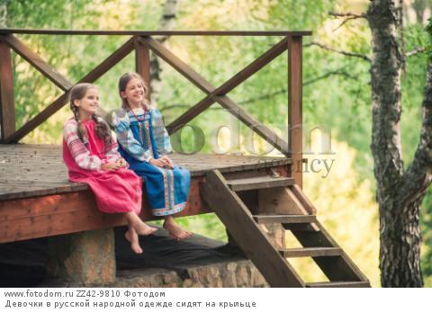 Девочки в русской народной одежде сидят на крыльце