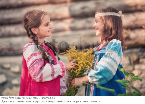 Девочки с цветами в русской народной одежде разговаривают