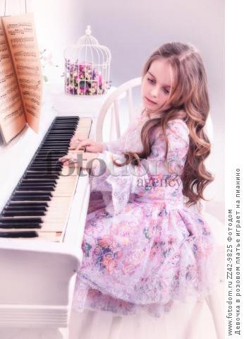 Девочка в розовом платье играет на пианино