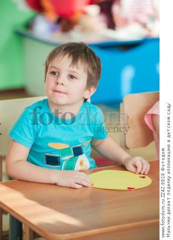 Мальчик делает поделку аппликацию в детском саду