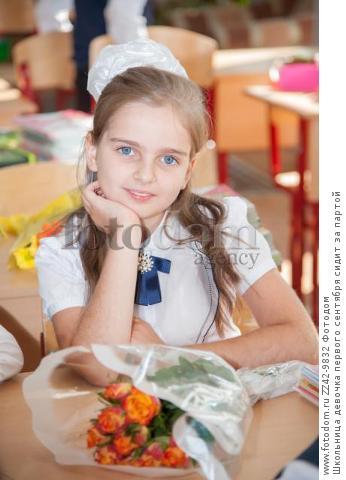 Школьница девочка первого сентября сидит за партой