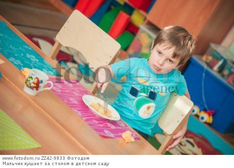 Мальчик кушает за столом в детском саду