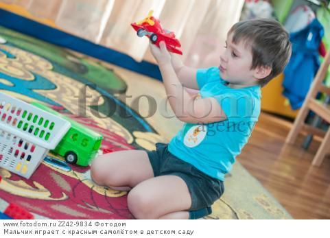 Мальчик играет с красным самолётом в детском саду